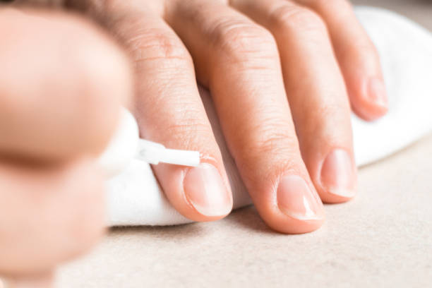 Female hand applying nourishing oil on cuticles